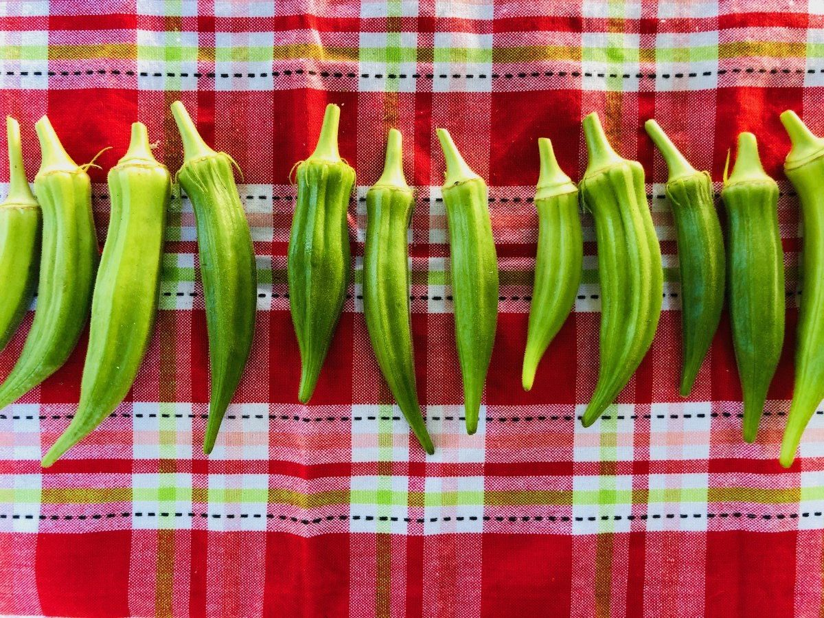 raw okra lined up on tablecloth